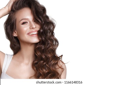 Beautiful young girl in white dress with natural make-up, hair curls and smile. Beauty face.