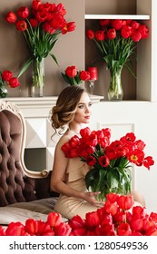 A beautiful young girl in a white dress is sitting on the sofa and holding a large bouquet of red tulips. March 8 concept. Morning of the bride