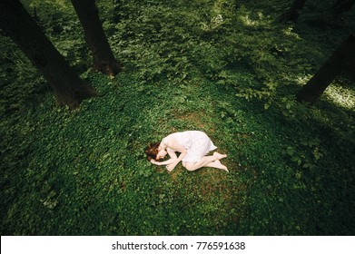 Beautiful young girl in white dress is sleeping in the woods outdoors