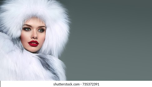 Beautiful young girl in a white fur hat and white fur coat with bright make-up and green eyes. Portrait.Fashion, beauty, warm clothes, fur, headdress, outerwear, bright make-up, winter, holiday.