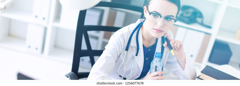 A beautiful young girl in a white robe is sitting at the computer desk, holding an open bottle of water and running.