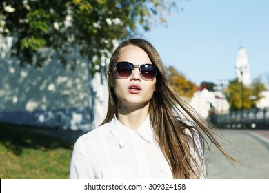 Beautiful young girl in a white shirt on the street in sunglasses on a sunny day