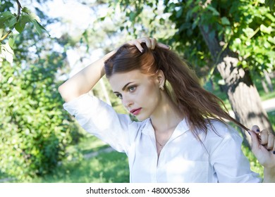 Beautiful young girl in a white shirt walking in the park.