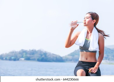 Beautiful young girl with white towel sitting on the road  drinking water from a plastic bottle after jogging and exercising outdoor.Sporty model ethnicity training indoor. Fitness,sport concept.