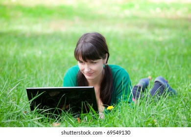beautiful young girl who lies with a laptop on a green lawn