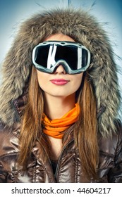 Beautiful young girl in winter clothes and dressed in fur hood  and snowboard goggles.