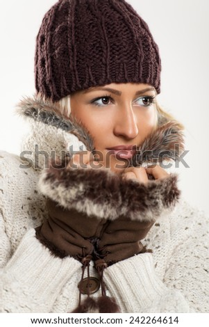4e891ac8bbca Beautiful young girl In winter clothes with a wool cap and fur gloves
