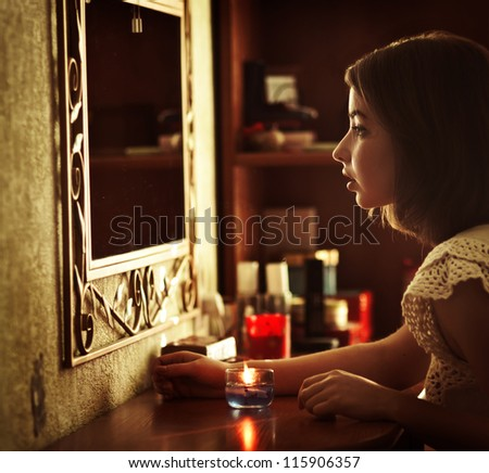 beautiful young girl wonders with a candle in front of a mirror
