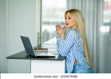 beautiful young girl working on herself with laptop at home in the kitchen