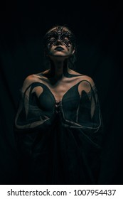 Beautiful young girl wrapped in transparent shawl with painted body and black mask on her face stands against black background. Body art.