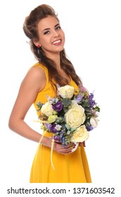 Beautiful young girl in a yellow dress with a bouquet of flowers