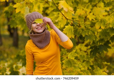 Beautiful young girl in a yellow dress and a knitted cap with a snuff stands among the yellow leaves in an autumn park