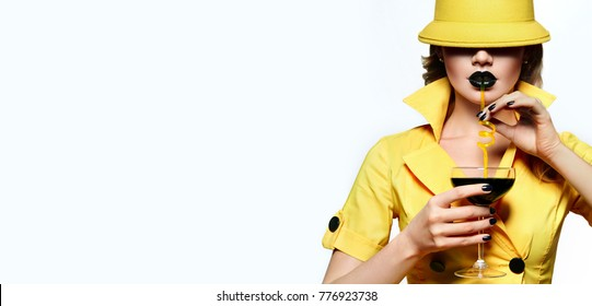 A beautiful young girl in a yellow hat and yellow dress is holding a glass with a black cocktail and a drink from a straw.Fashion, beauty, cosmetics, make-up, make-up artist, beauty salon business.