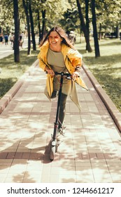 Beautiful young girl in a yellow raincoat riding an electric scooter, hoverboard, in orange sunglasses with long hair, street-style, city, smiles and pleasure, for fan, hipster, driver, emotional