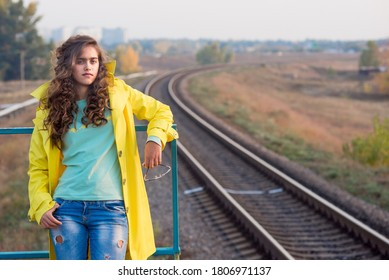 Beautiful young girl in yellow raincoat on a train platform waiting. curly girl in a yellow coat in the fall. Student train ride. Travel autumn.