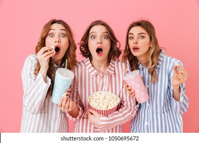Beautiful young girls 20s wearing colorful striped pyjamas having fun and eating pop corn during watching thrilling and exciting movie at home party isolated over pink background