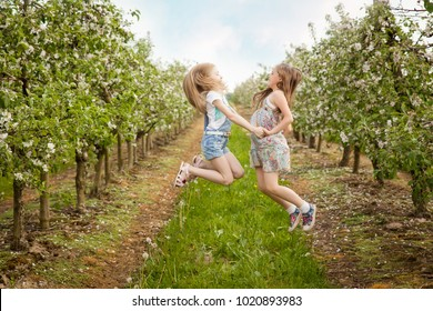 Beautiful young girls in blooming apple tree garden having fun and jumping in a warm spring day