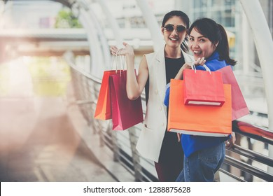 Beautiful young girls with colorful shopping bags over the path way to the shopping mall