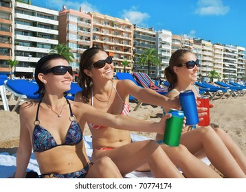 Beautiful young girls with drinks on beach. Costa Brava. Spain