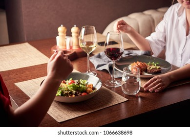Beautiful young girls with glasses of red wine in luxury restaurant
