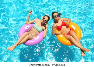 Beautiful young girls relaxing on inflatable rings in blue swimming pool