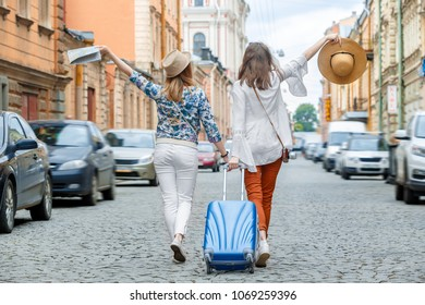 Beautiful young girls walking with blue suitcase on the street of old European city. A trip to Europe - dreams come true. Women are happy and enjoy the journey. They have suitcase and paper map.