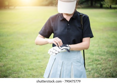 Beautiful young golfer Wearing gloves on a bright morning the golf course.