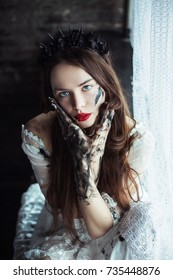Beautiful young gothic woman with the black flowers spikes crown on her head with torn tattered white dress and black painted hands . Mystery dark fantasy portrait