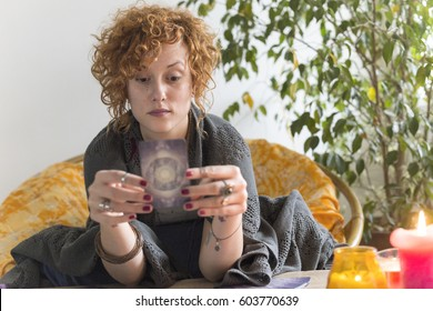 Beautiful young gypsy woman reading tarot cards