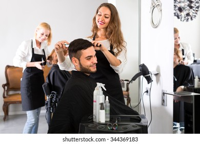 Beautiful young hairdresser working in a salon is making a haircut for a handsome man