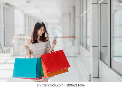 b5968c28e Beautiful young happy Asian woman with colorful shopping bag using  smartphone while shopping in mall