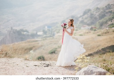 Beautiful young happy bride standing on the top of the mountain