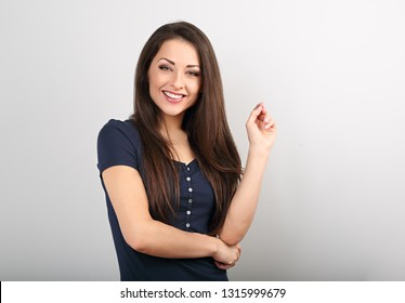 Beautiful young happy casual woman with finger under the face thinking and looking in blue shirt and long hair. Closeup