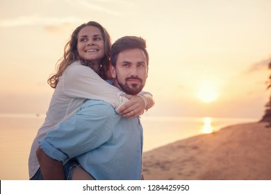 Beautiful young happy couple in love having fun on the beach at sunset during the honeymoon vacation travel, the guy carries the girl on yourself