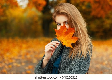 Beautiful young happy girl with a bright red-yellow autumn leaf in the park