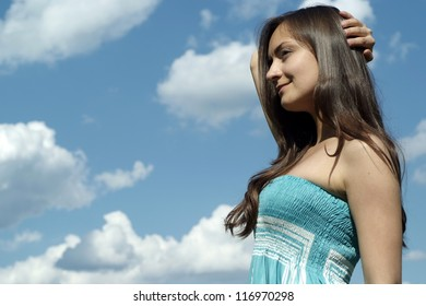 beautiful young happy girl standing against the sky