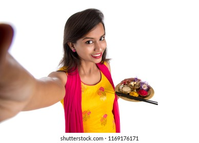 Beautiful young happy girl taking selfie with pooja thali using a mobile phone or smartphone on a white background