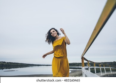 Beautiful young happy girl is walking along the railing of a construction in a bright dress