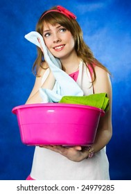 beautiful young happy housewife surprised with the softness ot the towels she has just washed