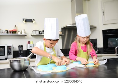 beautiful young happy kids boy and girl cooking and baking a cake in kitchen at home