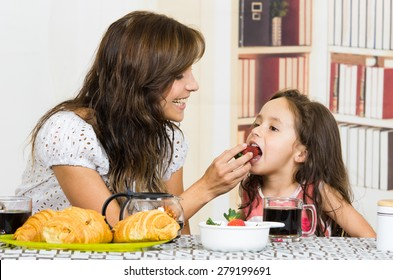 Beautiful young happy mom feeding fruit to cute little girl