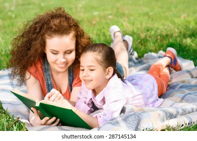 Beautiful young happy mother reading a green book with her small charming daughter lying on a plaid on a picnic in the park