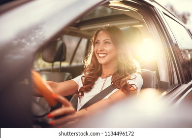 Beautiful young happy smiling woman driving her new car at sunset.  - Shutterstock ID 1134496172