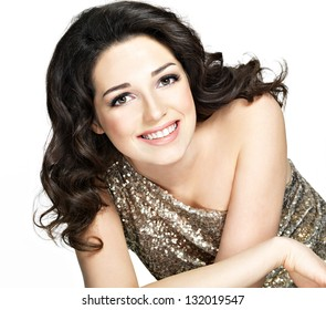 Beautiful young happy smiling woman with brown curly hairs poses at studio