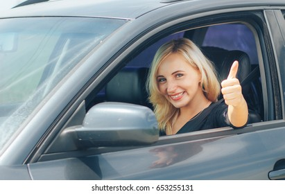 Beautiful young happy woman in car. Attractive blonde woman smiling.