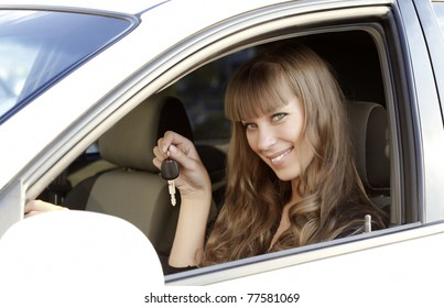 Beautiful young happy woman with car key.