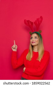 Beautiful young happy woman in christmas reindeer horns and red sweater is pointing up, looking away and smiling. Waist up studio shot on red background.