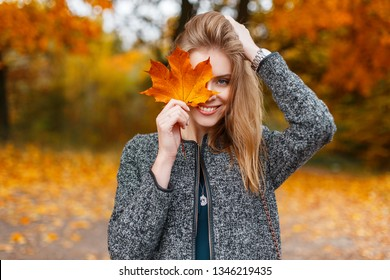 Beautiful young happy woman in a fashionable gray coat holding a bright yellow autumn leaf near the face in the park. Joyful girl model outdoors. Positive mood. Autumn day. Season.