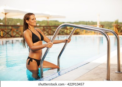 Beautiful young happy woman in getting out from the swimming pool