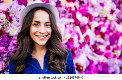 Beautiful young happy woman in hat on wall of flowers background